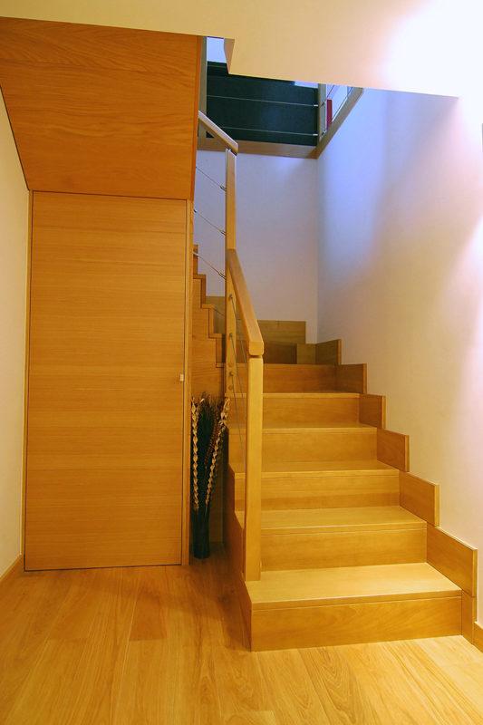 Escala amb fusta de roure, amb frontals i armari aprofitant el sota escala